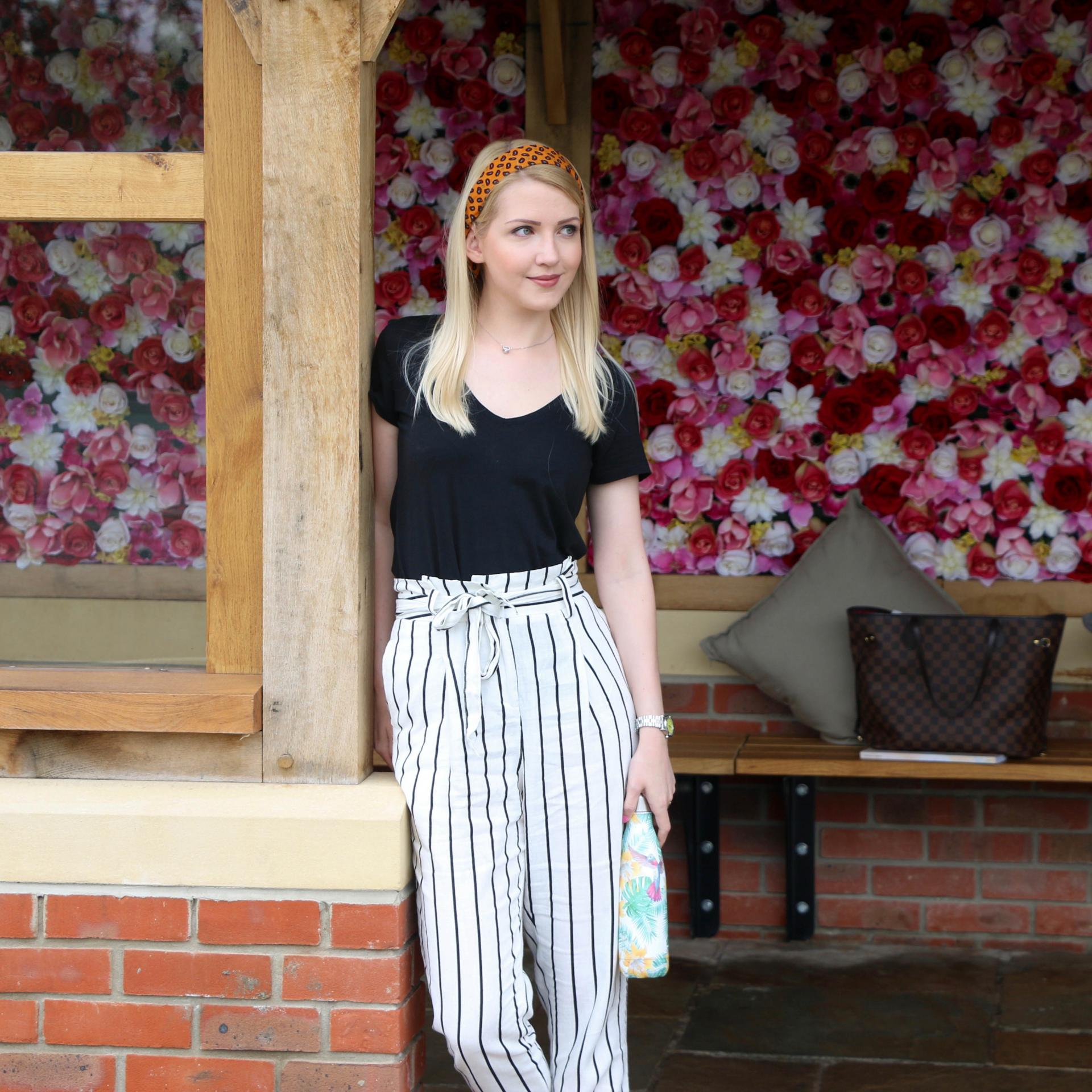 black top and black and white striped paper bag trousers and pink and red flower wall