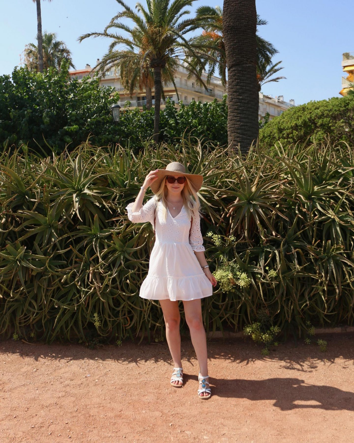 white summer embroidered dress and floppy summer hat in south of france